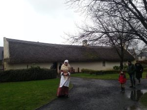 A costumed character acting as an eighteenth century villager stands outside the cottage.